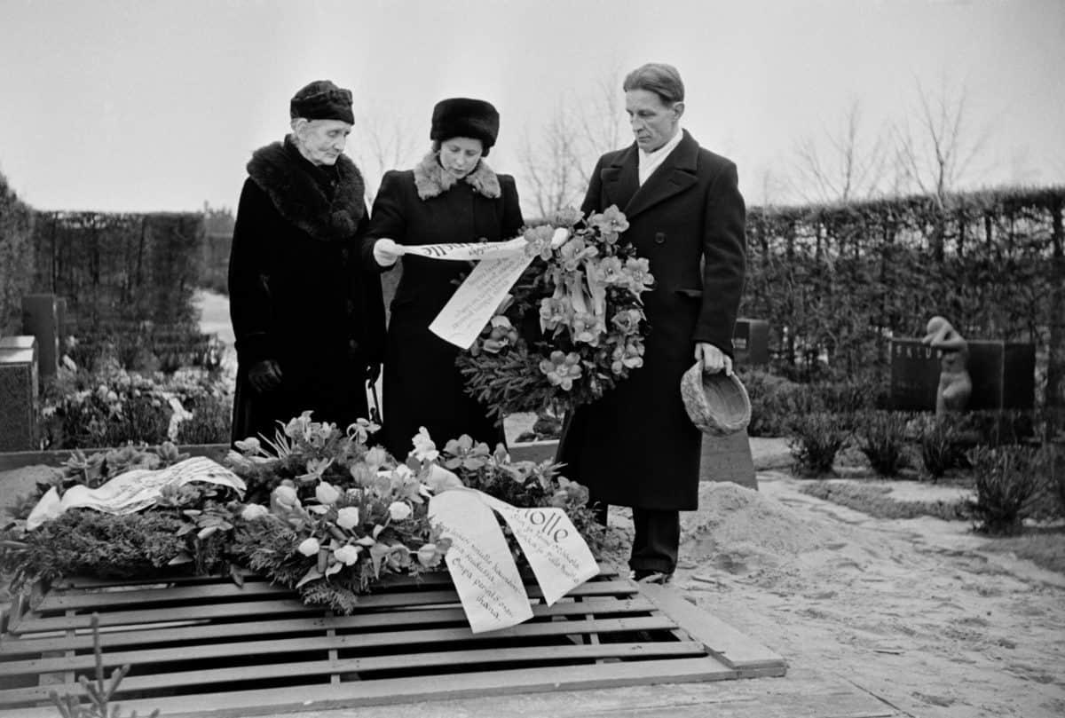 kaksi naista ja mies laskemassa seppelettä haudalle